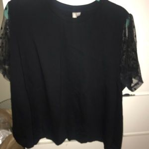 Black top with sheer polka dot sleeves.
